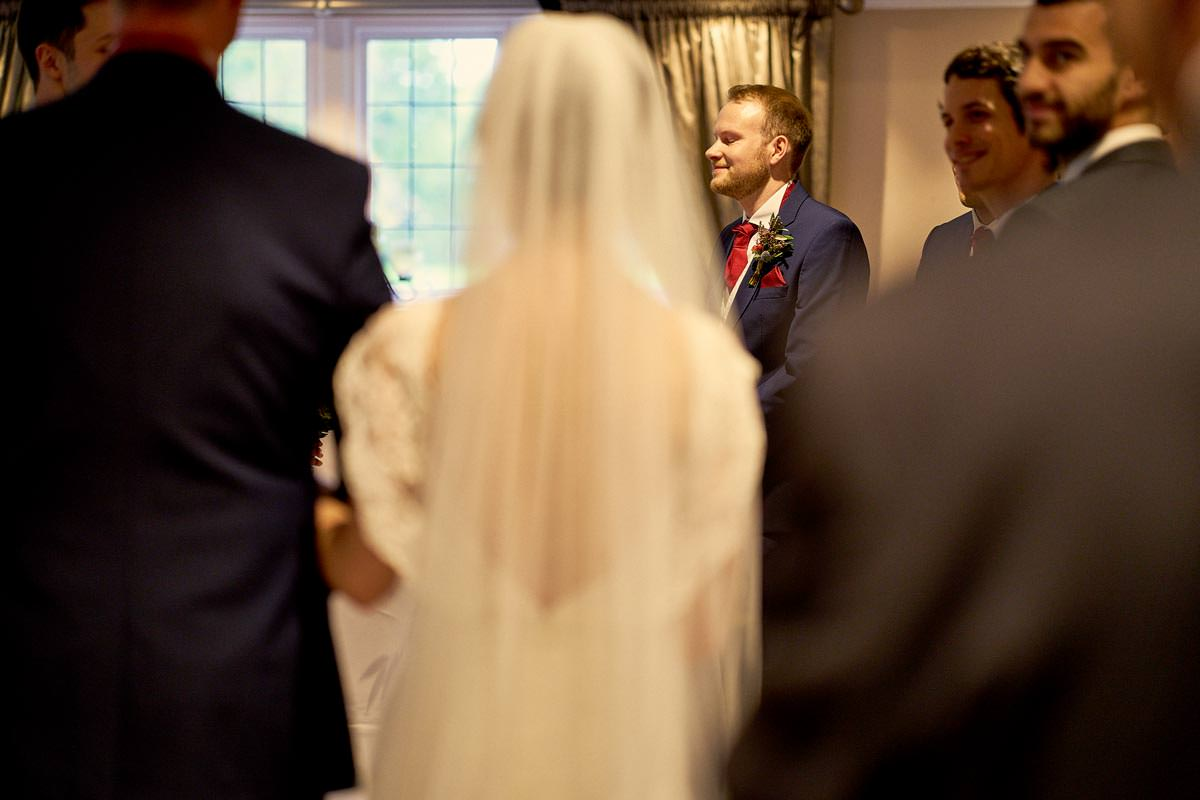 Groom smiling as bride walks down the aisle