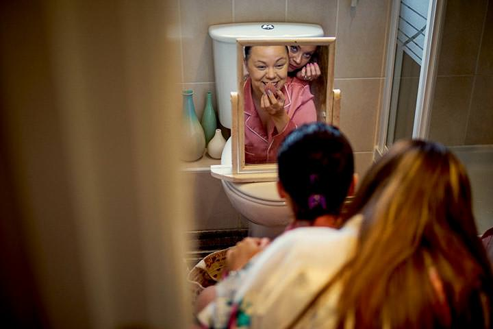Bridesmaid doing her makeup in front of the toilet