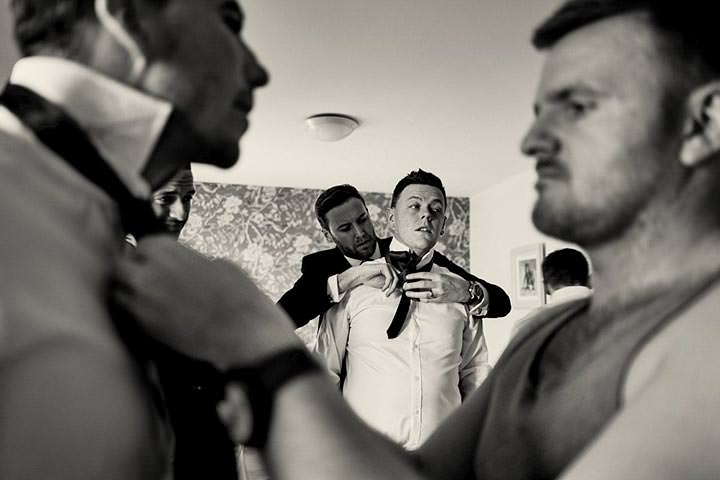 Grooms-men helping each other tie their ties