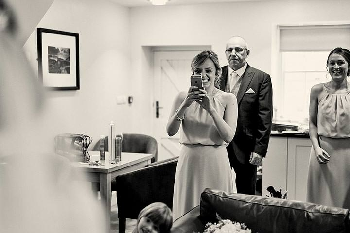 Bridesmaid and dad smiling at seeing bride for the first time