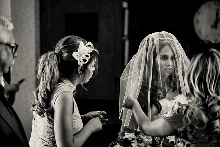 Bride looks nervous before wedding, veil over her face