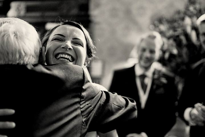 Bride smiling and hugging wedding guest