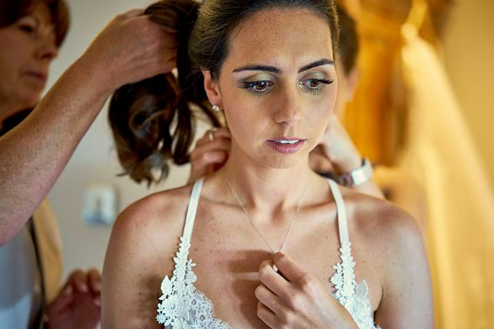 Bride looking nervous putting necklace on