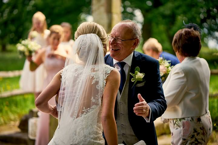 Father of the bride smiling at bride