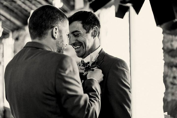 Groom laughing while having button hole put on