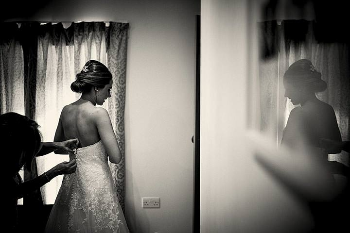 Bride having her dress buttoned up