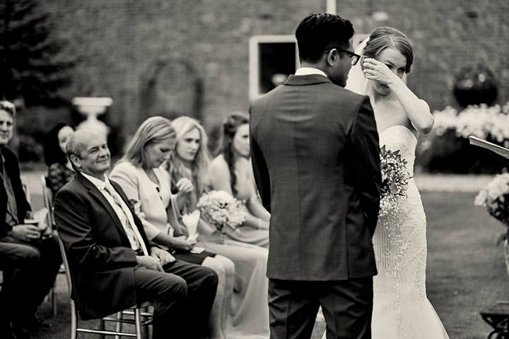 Bride wiping tears away during wedding ceremony