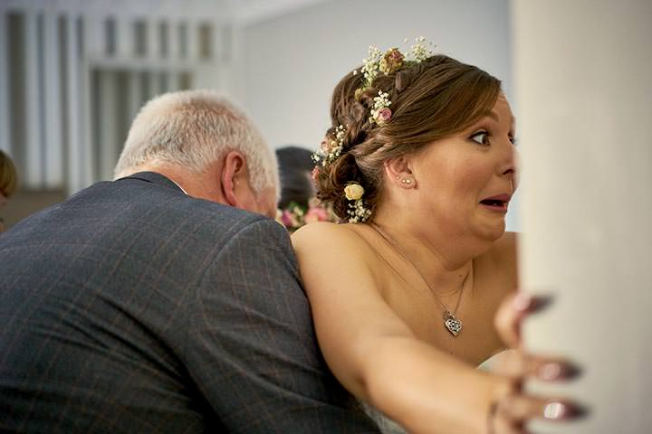 Bride pulling funny face as wedding dress is done up
