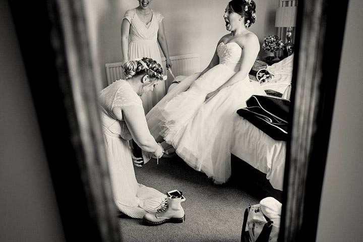 Bride getting help from bridesmaids to put doc martins on