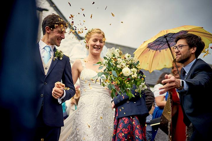 Bride & groom having confetti thrown at them outside Hafod Farm