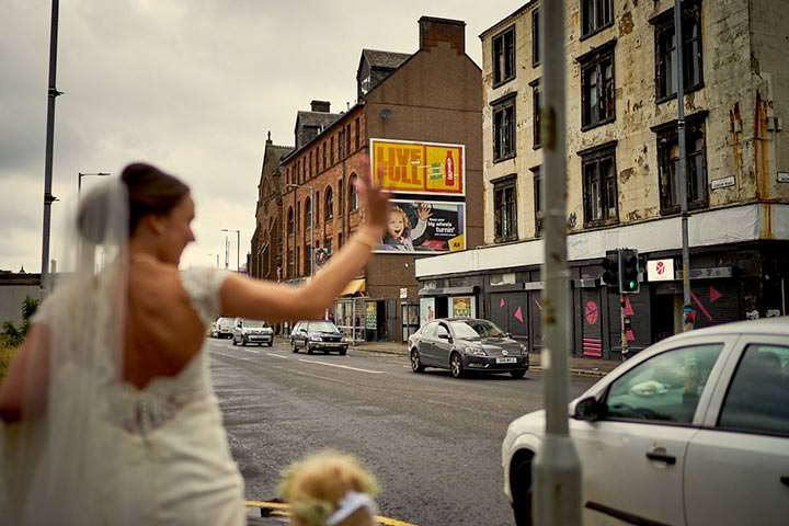 Bride waving as she walks the streets of Glasgow