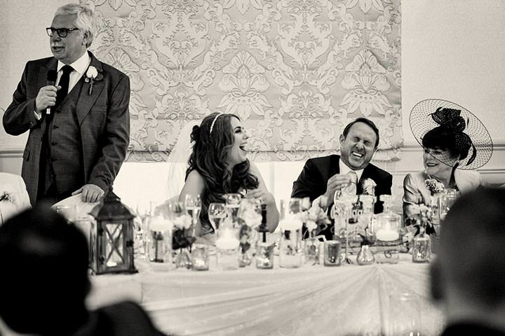 Groom laughing at father of the bride speech