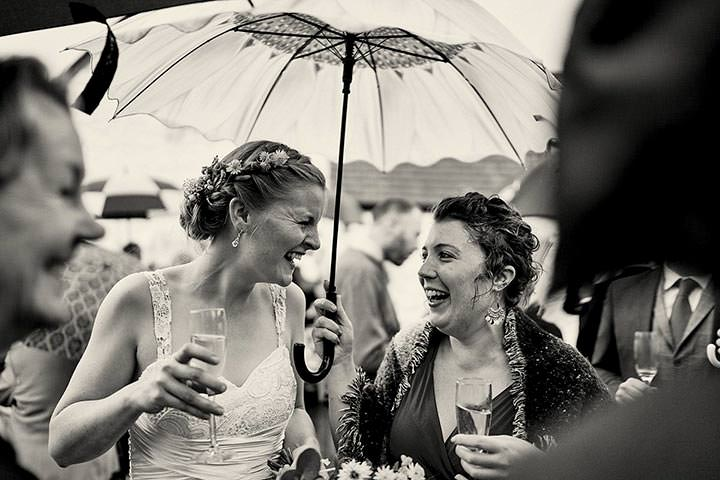 Bride laughing with guests under umbrella