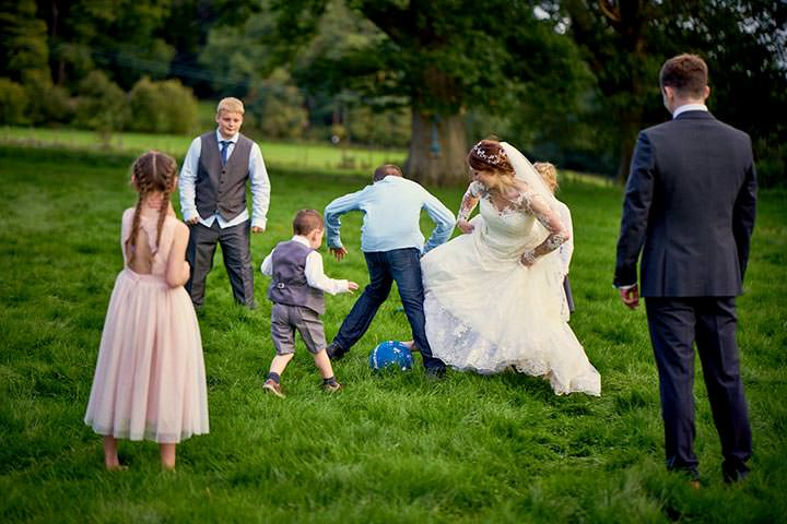 Bride playing football in wedding dress