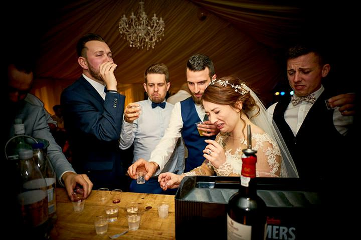 Bride doing shots with wedding guest