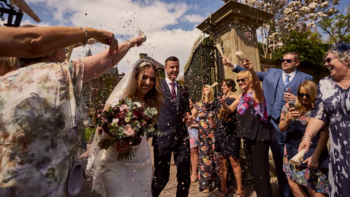 Bride & groom having confetti thrown at them when leaving Soughton Hall
