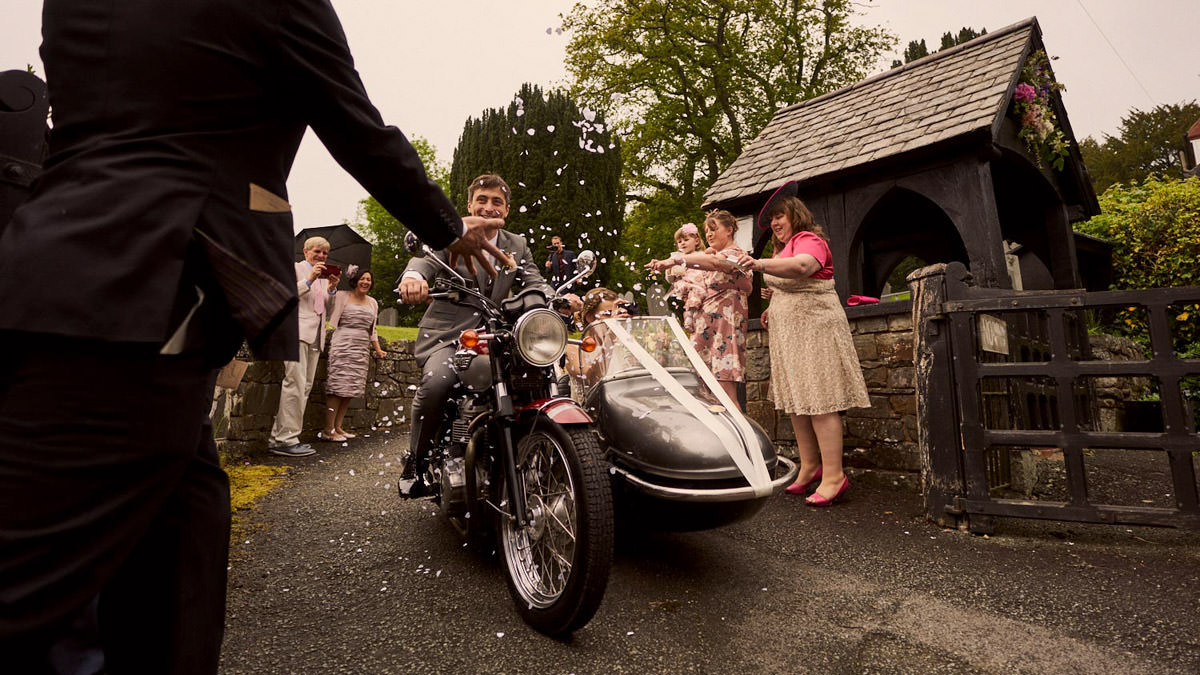 Bride & groom leaving the church in a motorbike and sidecar