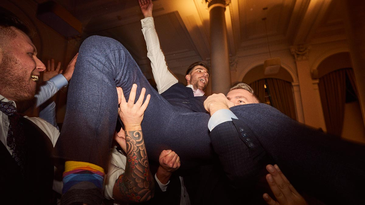 Groom crowd surfing at the end of a Scottish wedding