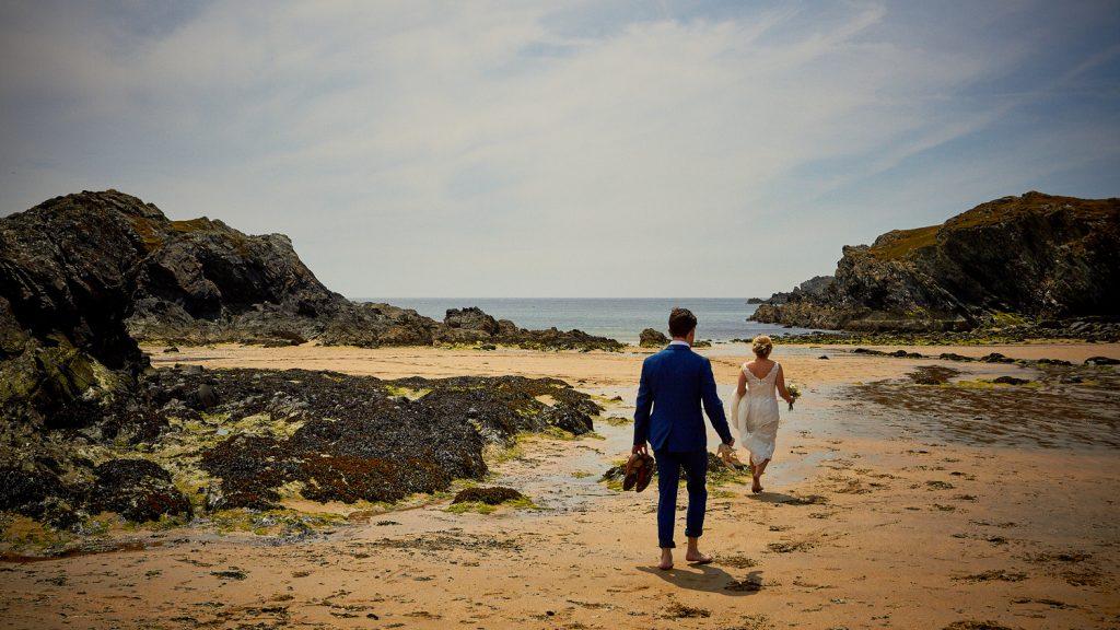 Bride & Groom stroll on the beach.