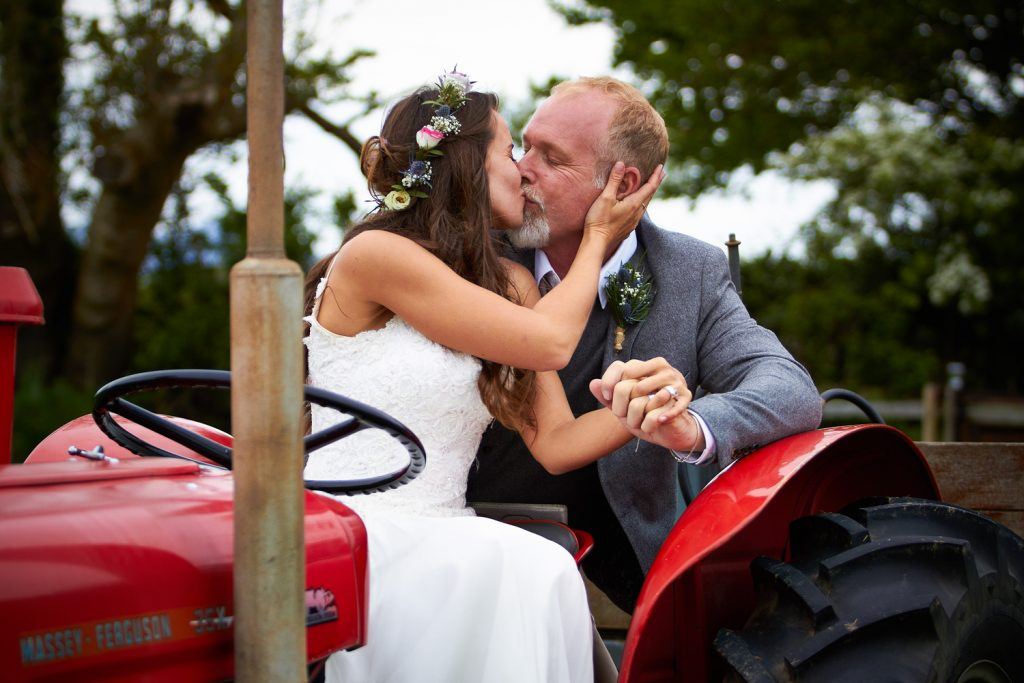 Bride & Groom kissing on a tractor