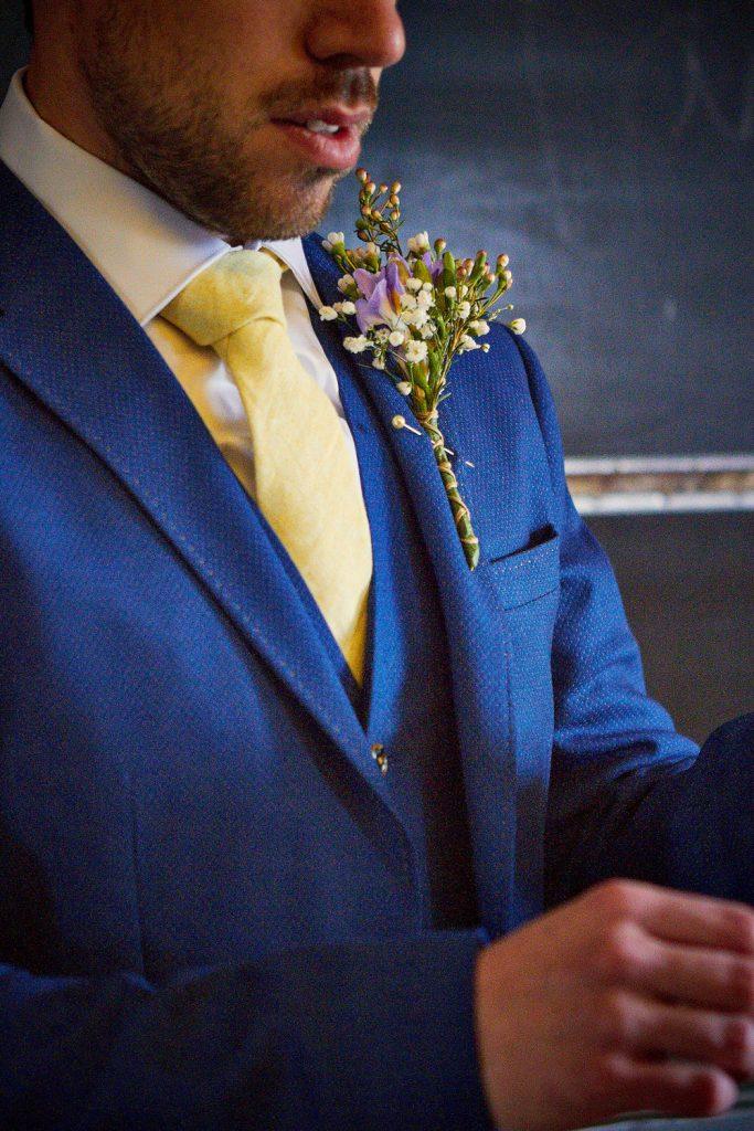 blue suit, wild flower button hole