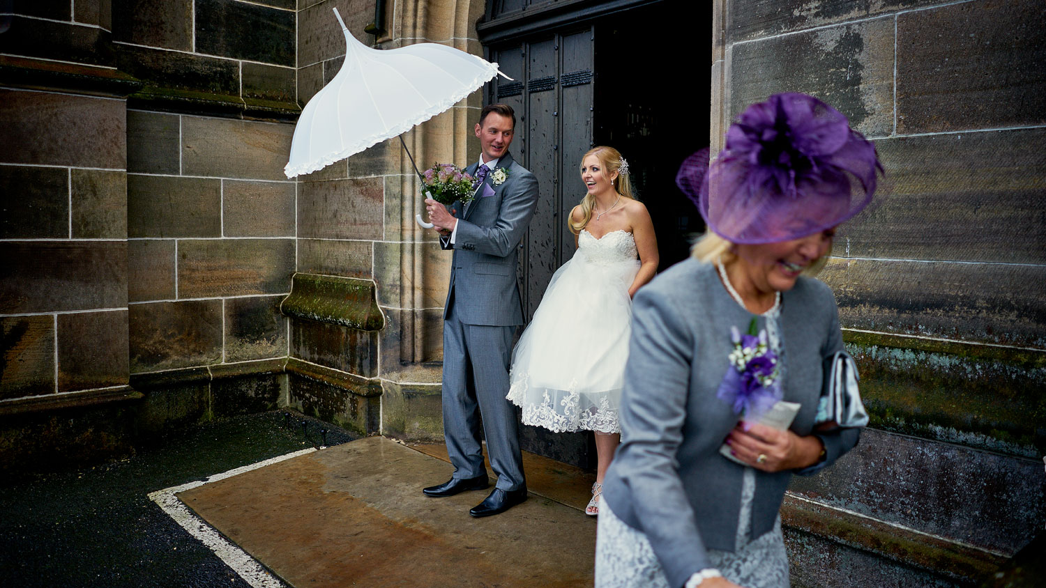 Bride, Groom, Mother of the Bride and an umbrella