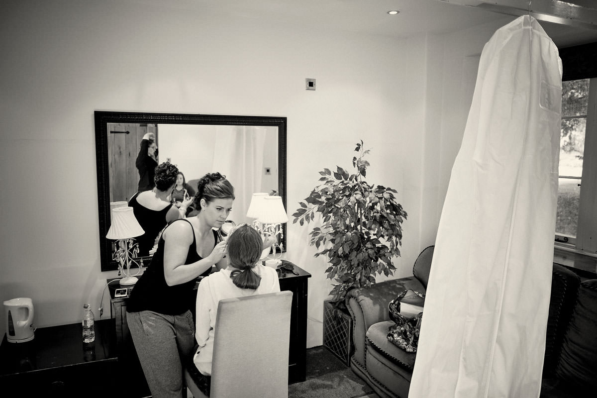 bride having her make up done in front of the mirror