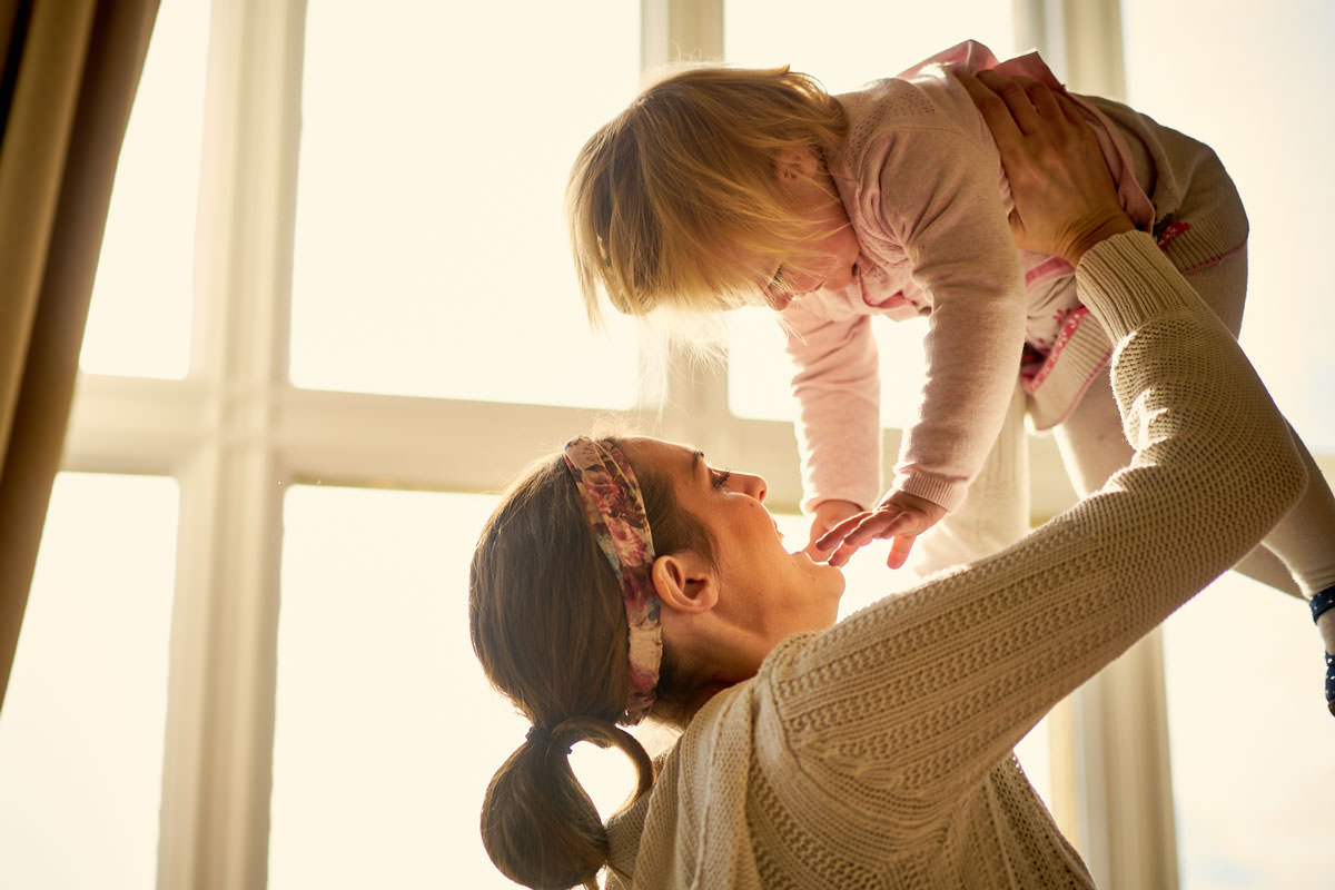 bride playing with her daughter on wedding morning