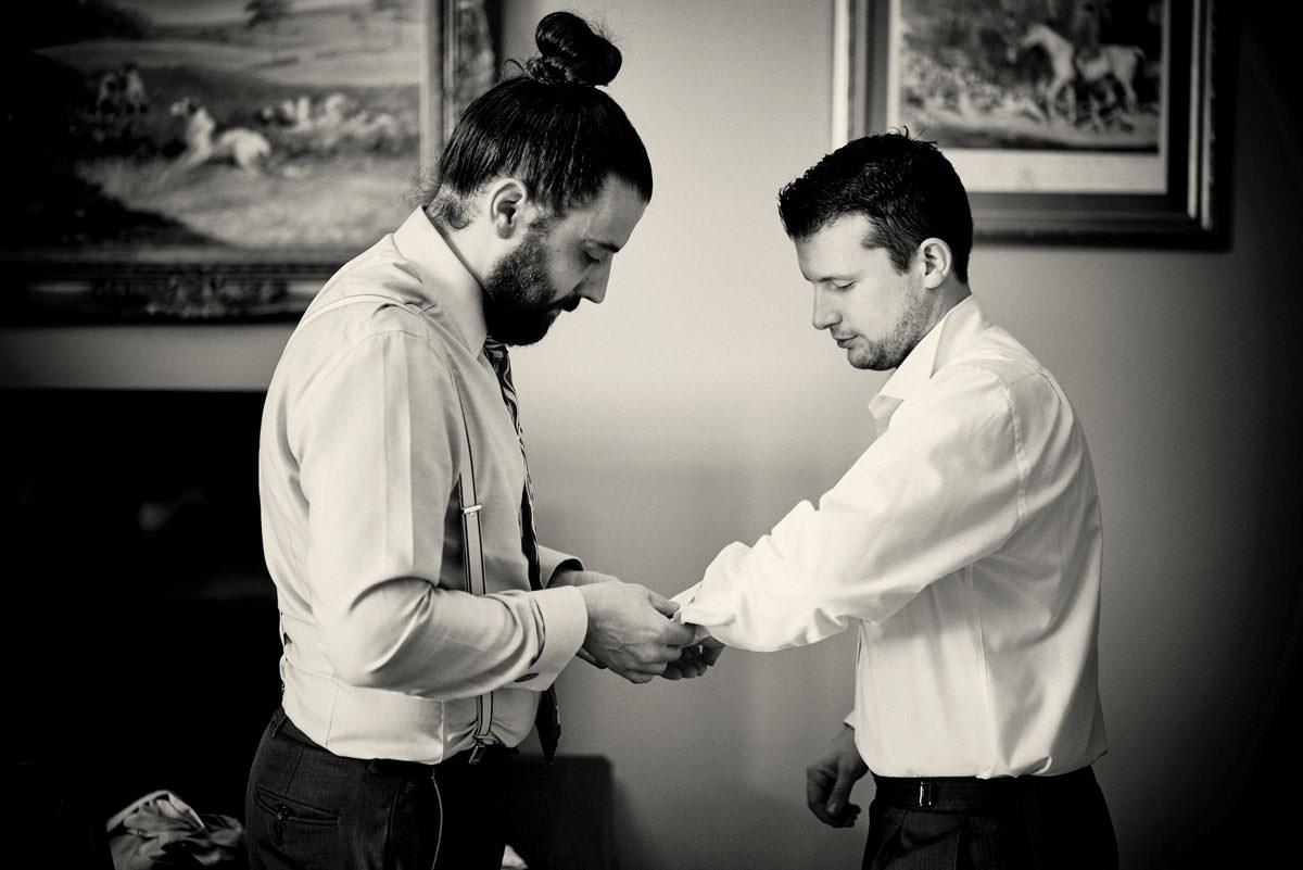 best man helping groom put on cuff links