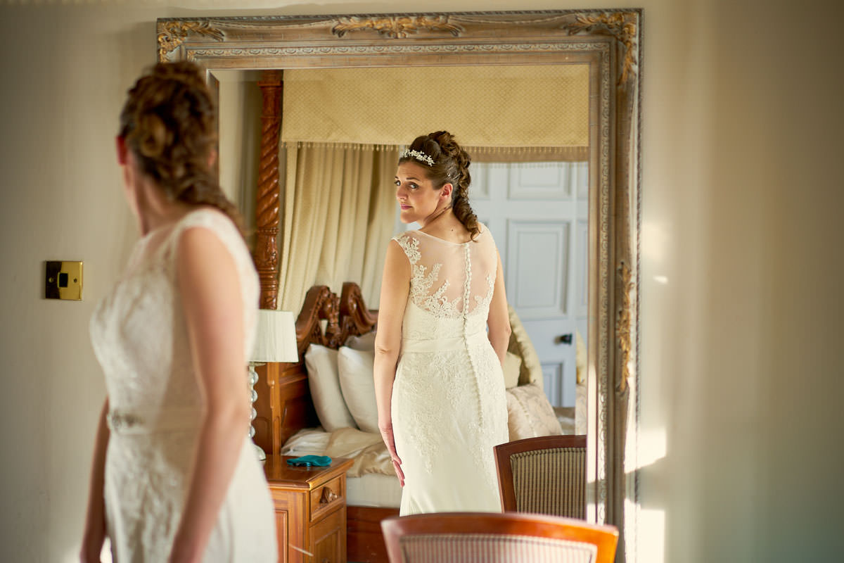 bride looking at her dress in the mirror