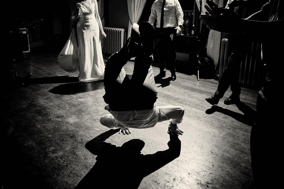 groom doing at backflip at wedding