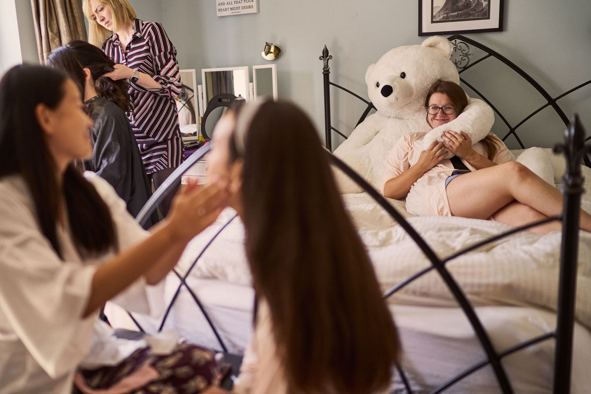 bridesmaid sitting on a bed with giant teddy while bride puts makeup on another bridesmaid