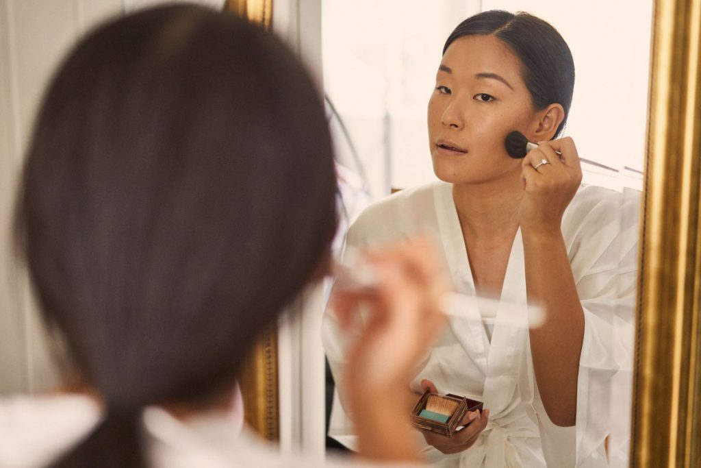 reflection of Bride putting on her own make up
