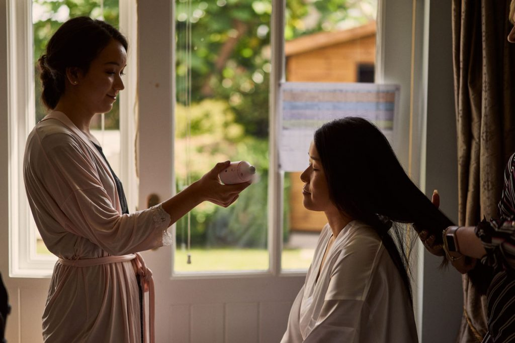 Bridesmaid fanning Bride while she has her hair done