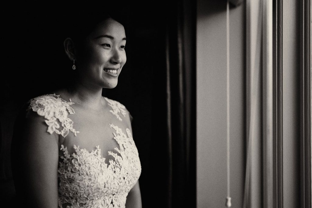 happy bride smiling as she gets into her wedding dress