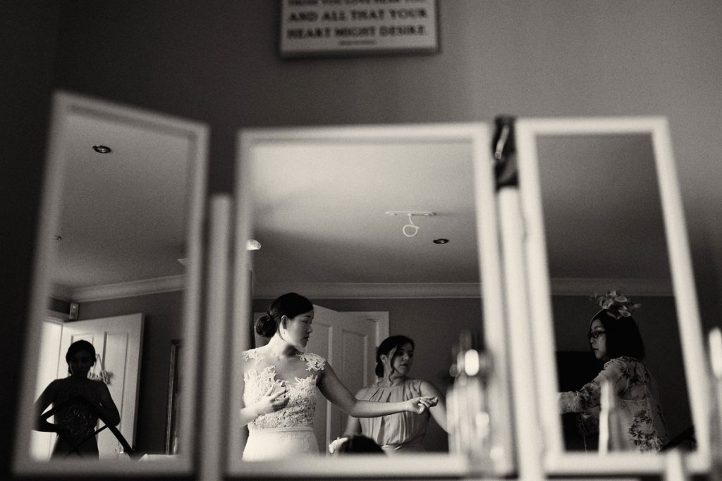 reflection of Bride and Bridesmaids in the mirror as they get into the wedding dress
