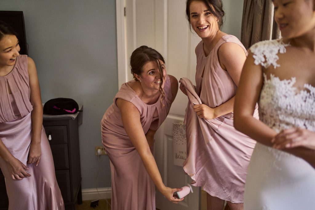 Bridesmaids holding a fan up another Bridesmaids dress as it was really hot