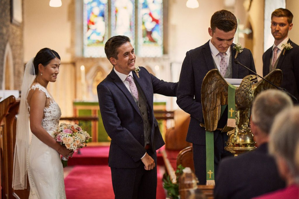 Groom giving Best Man a reassuring hug while he does his reading