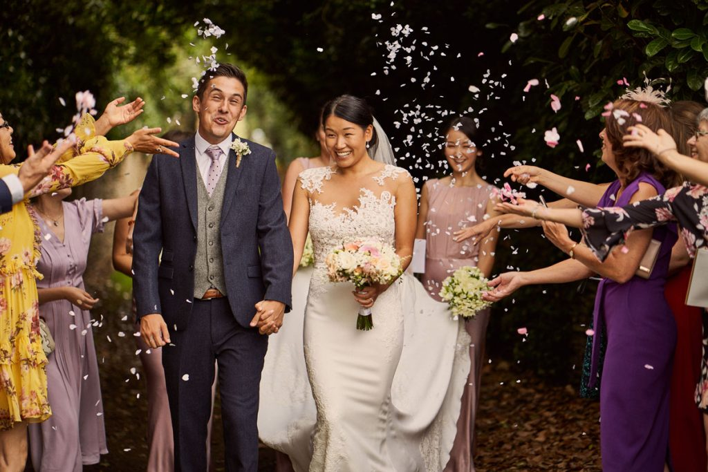 Bride & Groom pulling funny faces as wedding guest throw confetti at them