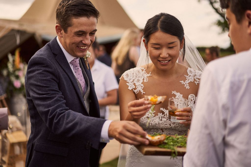 Bride & Groom having canapés in a sunny Yorkshire filed
