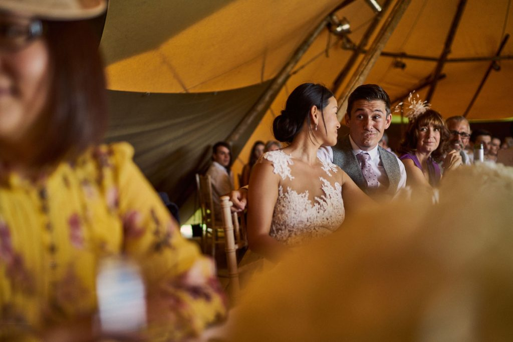 groom pulling funny face at his wife during Best Man speech
