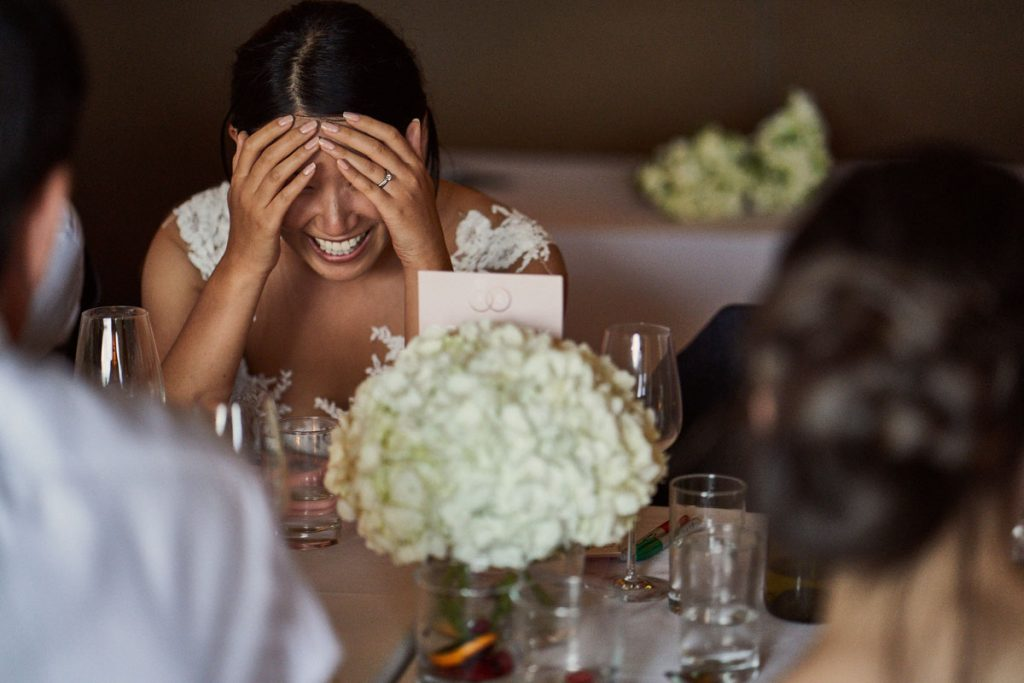 bride hiding her face with embarrassment at Groom's speech