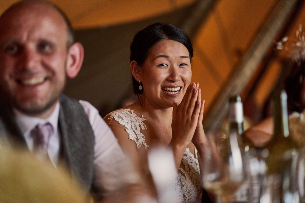 Bride crying with laughter at her husbands speech
