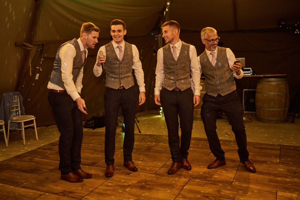 grooms dad and Best Men perform a song as a surprise for Bride & Groom