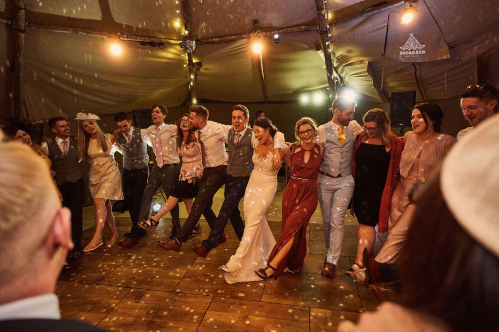 Bride & Groom and wedding guest all linking arms on the dance floor