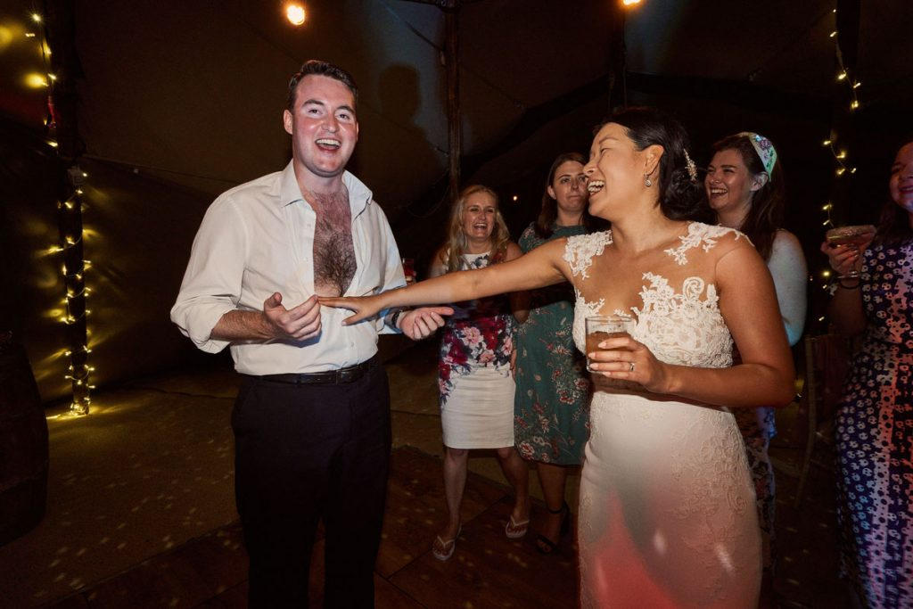 bride helping wedding guest take his shirt off