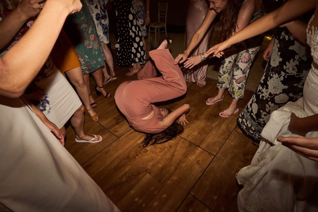 wedding guest doing a forward roll on the dance floor