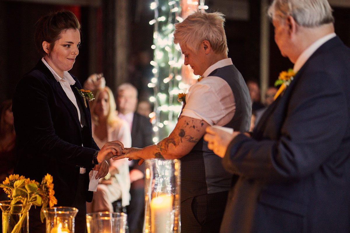 brides changing rings by candle light at Victoria Warehouse