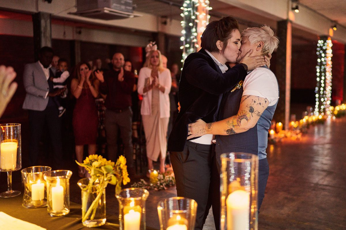 two brides just married having their firs t kiss