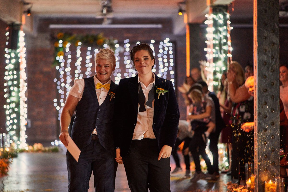 two happy smiling brides walk back down the aisle after they've pronounced married